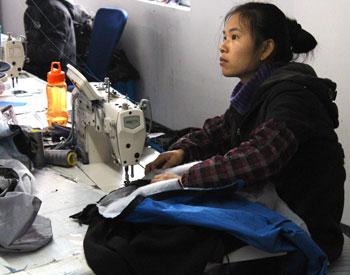 Bilde av en kvinnelig tekstilarbeider som syr.
