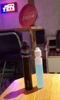 En vape (e-sigarett) og en flaske vapejuice avbildet i en bar